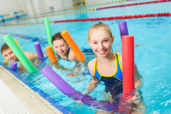 Two girls in swimming pool with water noodles