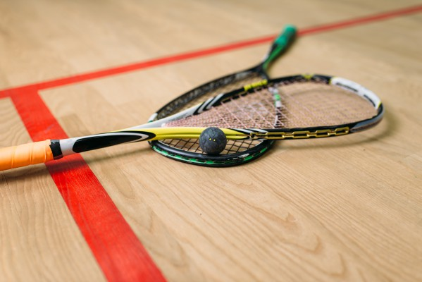 Two squash racquets with ball on squash court