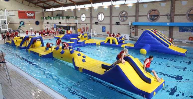 Kids climbing over inflatable pool activity