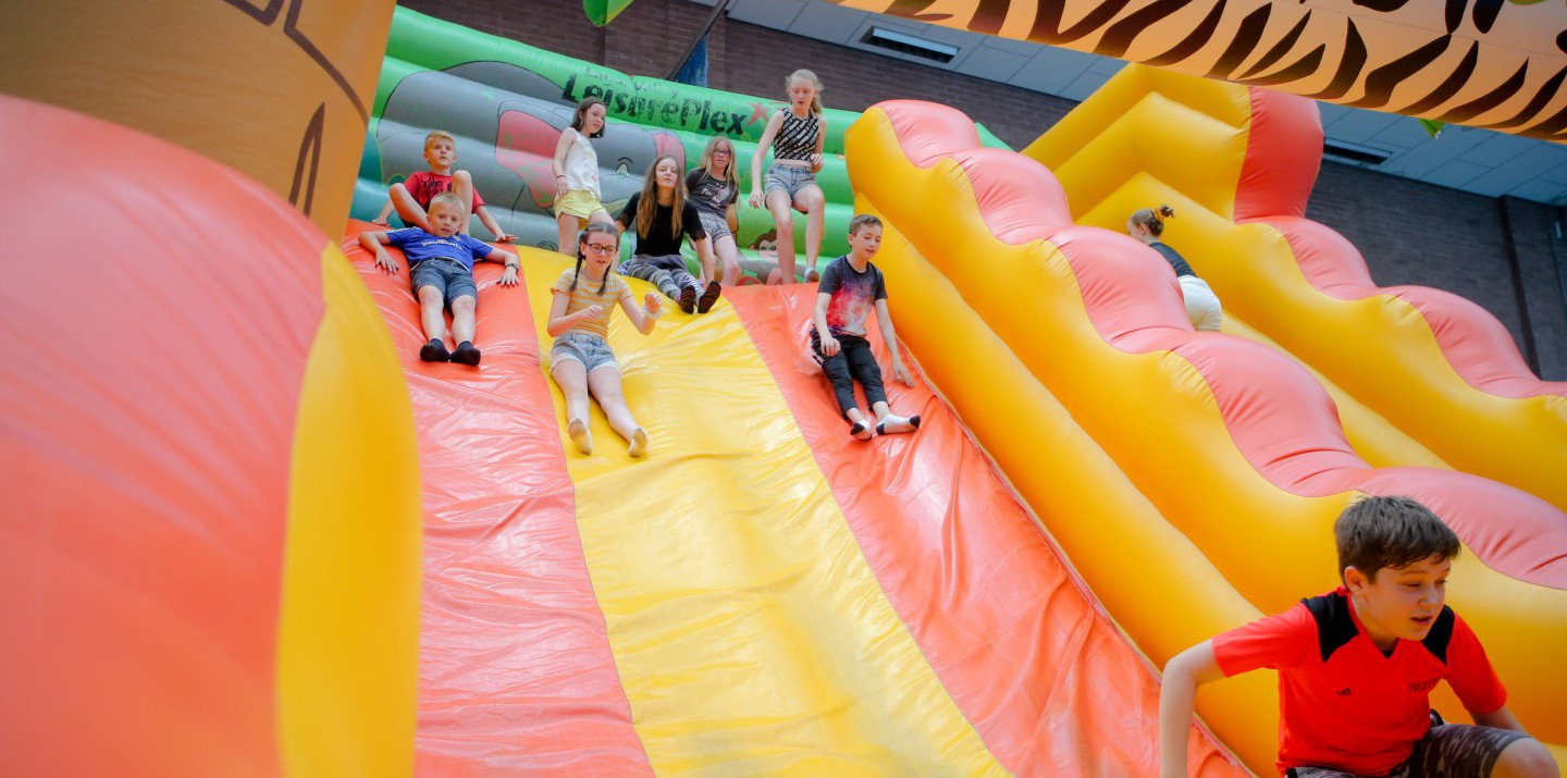 Children on bouncy castle slide